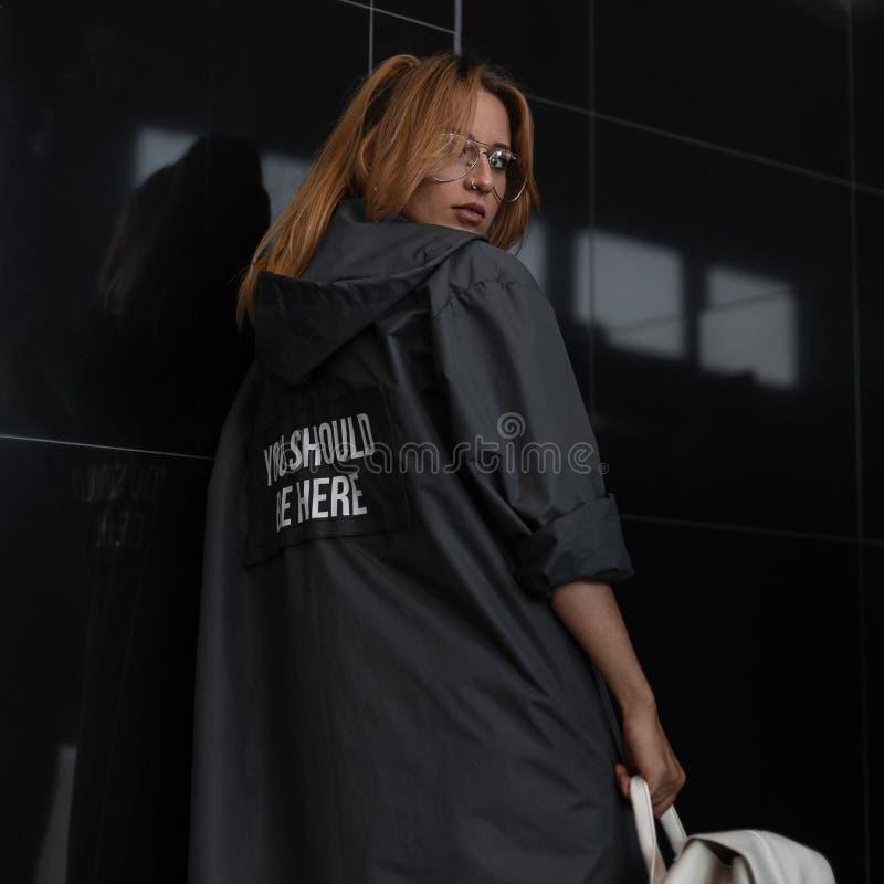 Moderno novo bonito da mulher do ruivo em uma capa de chuva elegante com a capa em vidros à moda com uma trouxa à moda do vintage fotografia de stock royalty free