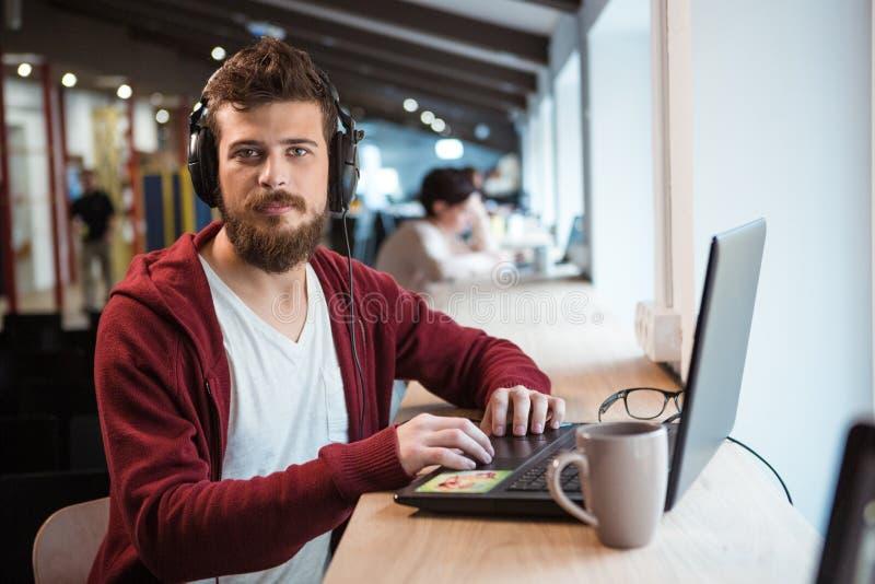 Moderno novo com a barba nos fones de ouvido que trabalham usando o portátil imagem de stock