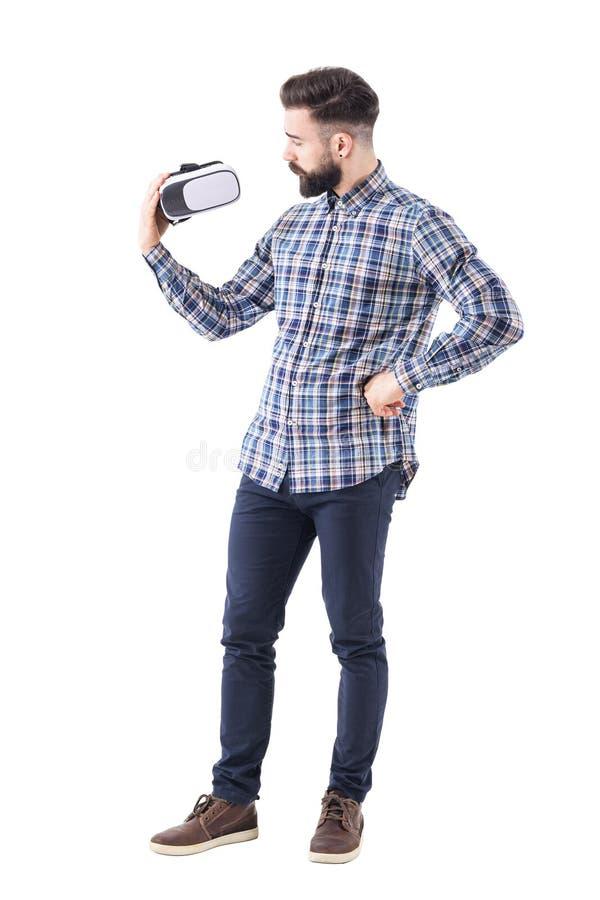 Moderno novo farpado cético na camisa de manta que examina vidros da realidade virtual imagem de stock