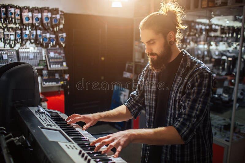 Moderno novo sério e concenrated para sentar-se e jogar no teclado Está sozinho na sala Está ensolarado para dentro foto de stock