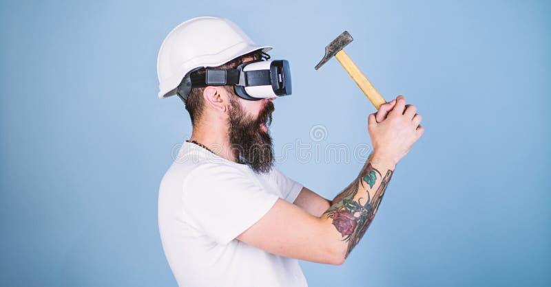 Moderno ocupado com renovação na realidade virtual O homem com a barba em vidros de VR guarda o martelo, luz - fundo azul guy fotos de stock