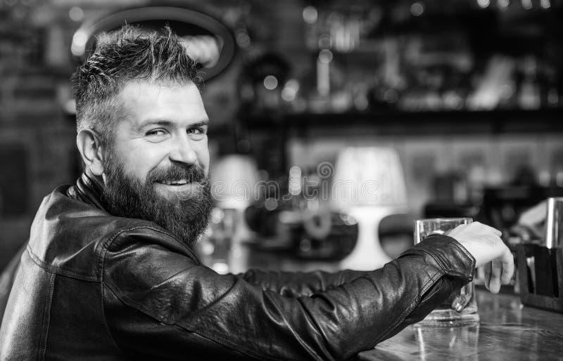 Moderno que relaxa na barra com cerveja O homem farpado do moderno brutal senta-se na cerveja da bebida do contador da barra Sext imagem de stock