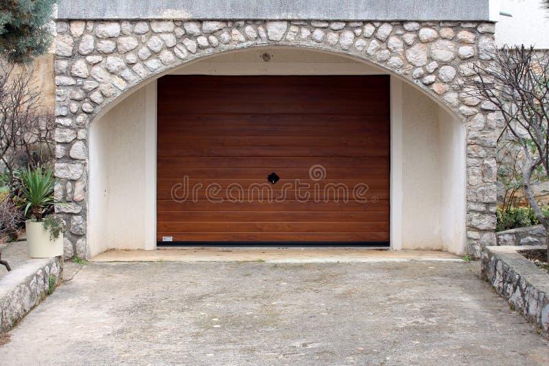 Moderno ruede para arriba la puerta del garaje del metal con falso final de grano de madera imagen de archivo
