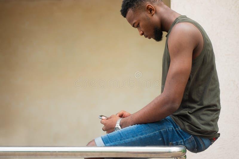 Moderno, um homem novo que usa um smartphone Adolescente afro-americano que guarda um smartphone móvel que senta-se nos trilhos foto de stock royalty free