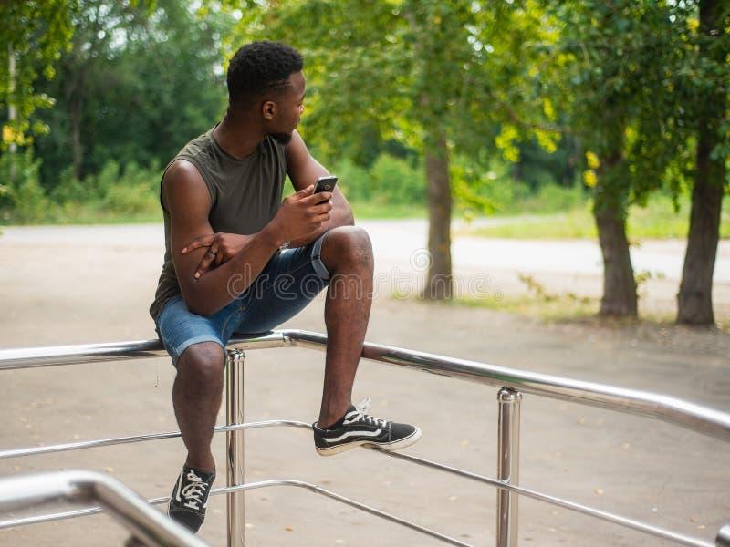 Moderno, um homem novo que usa um smartphone Adolescente afro-americano que guarda um smartphone móvel que senta-se nos trilhos imagens de stock royalty free