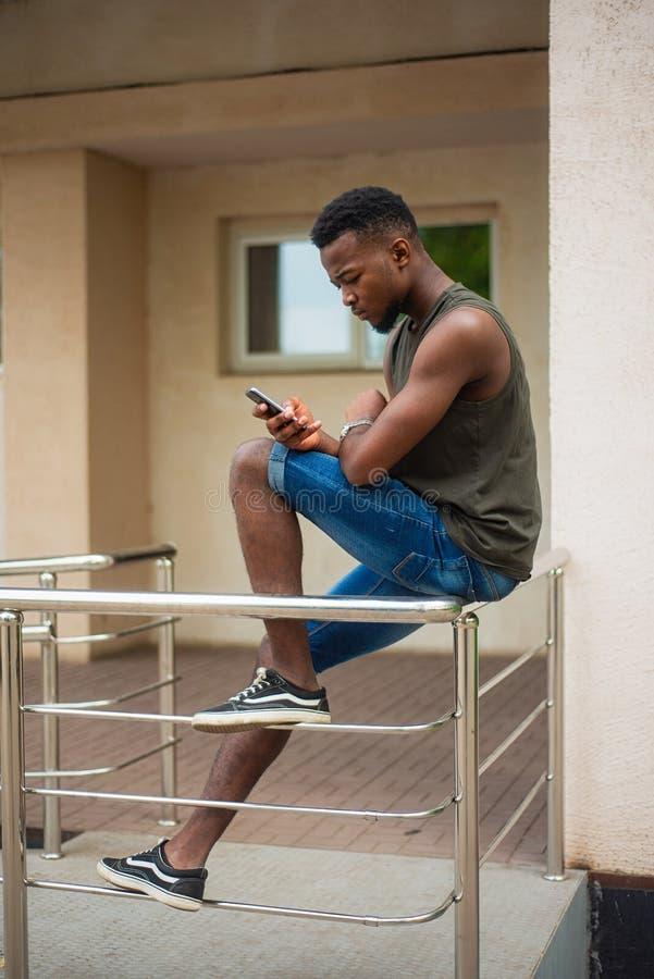 Moderno, um homem novo que usa um smartphone Adolescente afro-americano que guarda um smartphone móvel que senta-se nos trilhos fotografia de stock royalty free