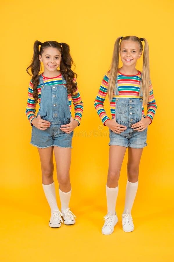 Moderno y elegante Niñas pequeñas con ropa de arco iris Ropa de juego Tienda de moda Debe tener accesorio Vibrante imagenes de archivo