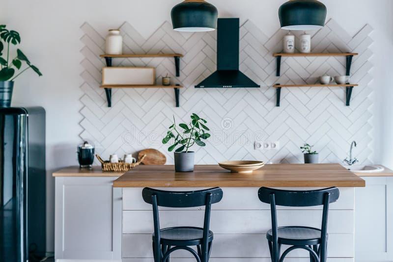 Moderno y luminoso interior de cocina con muebles blancos y mesa de comedor imagenes de archivo