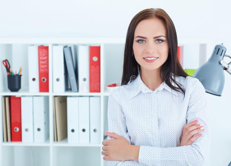 Modernt anseende för affärskvinna med korsade armar och se rakt till kameran i kontoret med kopieringsutrymme fotografering för bildbyråer