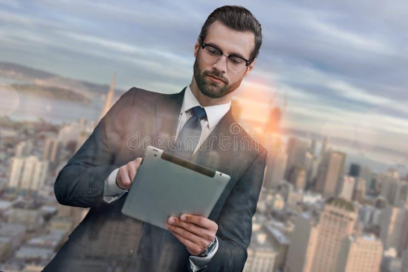 modernt använda för teknologier Stilig skäggig affärsman i dräkt genom att använda den digitala minnestavlan, medan stå utomhus m royaltyfri bild