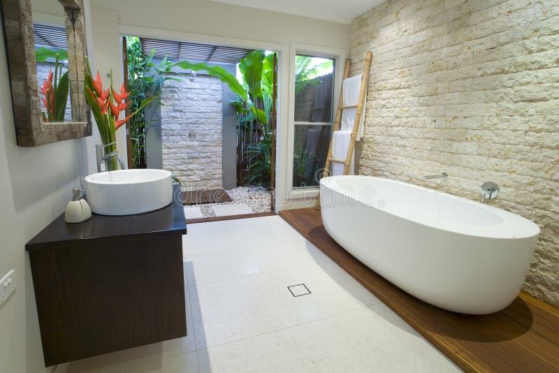 Modernt asiatiskt badrum med timmerdäcket royaltyfri bild