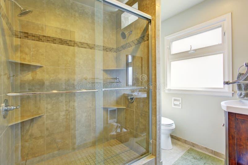 Modernt badrum med den glass dörrduschen royaltyfria foton