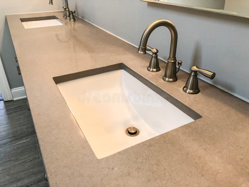 Modernt badrum med kvartscountertopen, två vaskar och vattenkranar med stengolvet royaltyfri foto