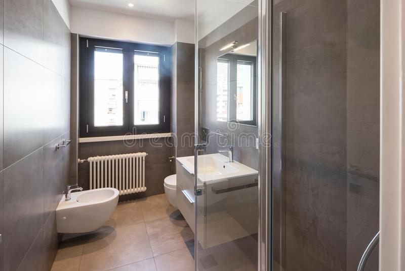 Modernt badrum med stora tegelplattor royaltyfri foto