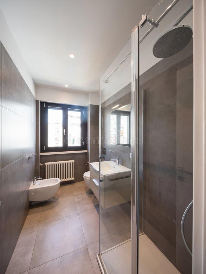 Modernt badrum med stora tegelplattor fotografering för bildbyråer