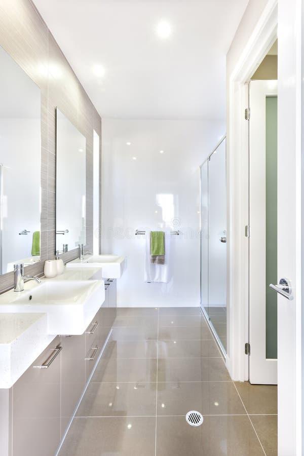 Modernt badrum med upps?ttningen av lavoarer och badrummet arkivfoto