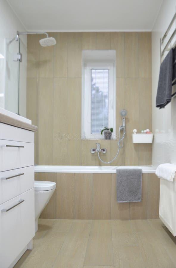 Modernt badrum som är inre med vita beigea tegelplattor och ett bad bild royaltyfri foto
