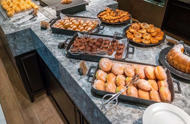Modernt bageri med sortimentet av bröd, kakor och bullar på ett hotell royaltyfri foto