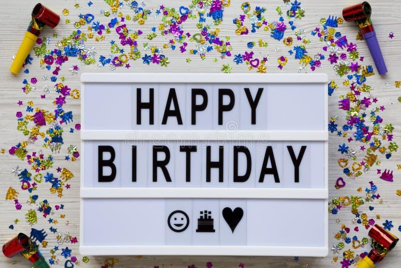 Modernt bräde med text 'lycklig födelsedag ', garneringparti på vit träbakgrund, över huvudet sikt Lekmanna- lägenhet, bästa sikt royaltyfri foto