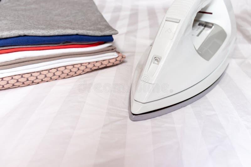 Modernt elektriskt vitt järn nära en bunt av kläder stänger sig upp med kopieringsutrymme - att stryka, tvätterit och hushållsarb royaltyfria bilder