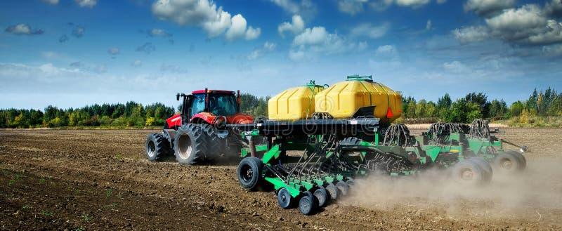 Modernt grönt fältarbete för traktor på våren royaltyfri foto
