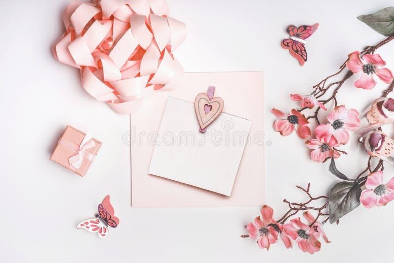 Modernt hälsa kort som är falskt upp med blommablomningen, bandet, den lilla gåvaasken och hjärtor i korallfärg på vit bakgrund,  arkivbilder