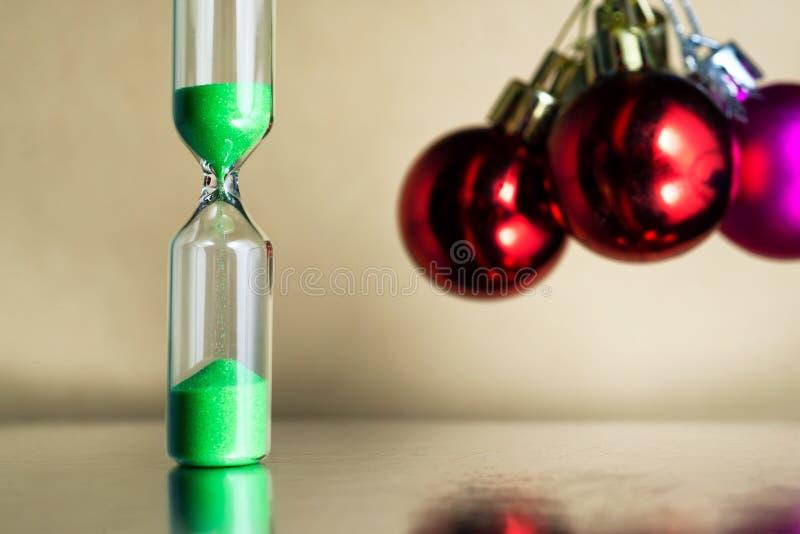 Modernt härligt grönt timglas med jul eller bollar för xmas och för nytt år royaltyfria bilder