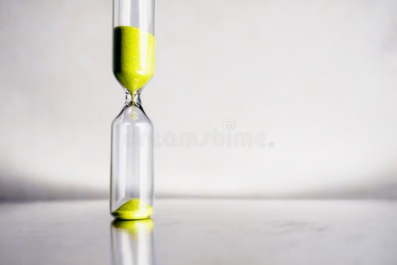 Modernt härligt gult timglas med ljus bakgrund för kopieringsutrymme Övergående begrepp för timglastid för affär arkivfoton