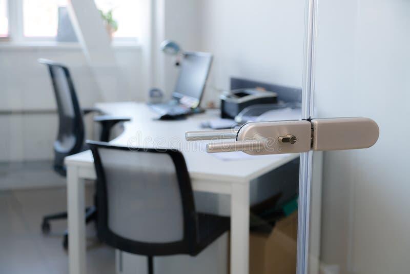 Modernt modernt handtag för exponeringsglasdörrlås med det moderna affärskontoret i bakgrunden royaltyfri foto