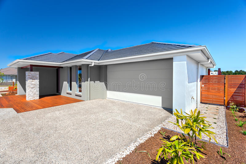 Download Modernt Hus Med Ett Garage- Och Trädgårdområde Och Blå Himmel Arkivfoto - Bild av staket, ytter: 76703340