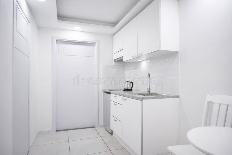 Modernt inre vitt kökrum med den inbyggde möblemangmodellen ställer ut för boutiquehotellrum arkivfoton