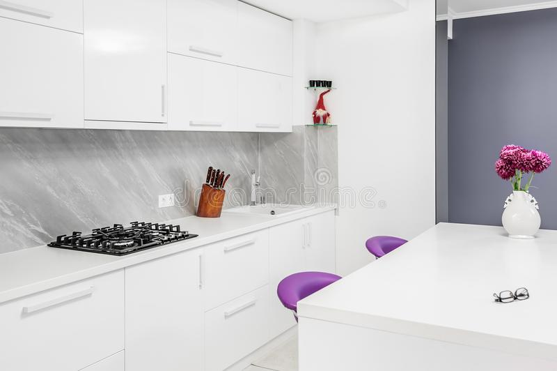 Modernt kök med att äta middag tabell- och lilastolar arkivfoton