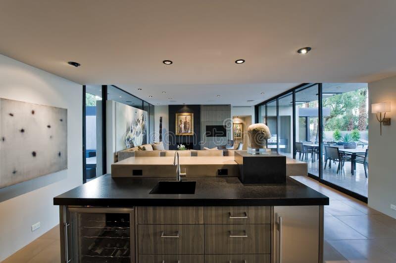 Modernt kök med vardagsrum och farstubron bakom fotografering för bildbyråer