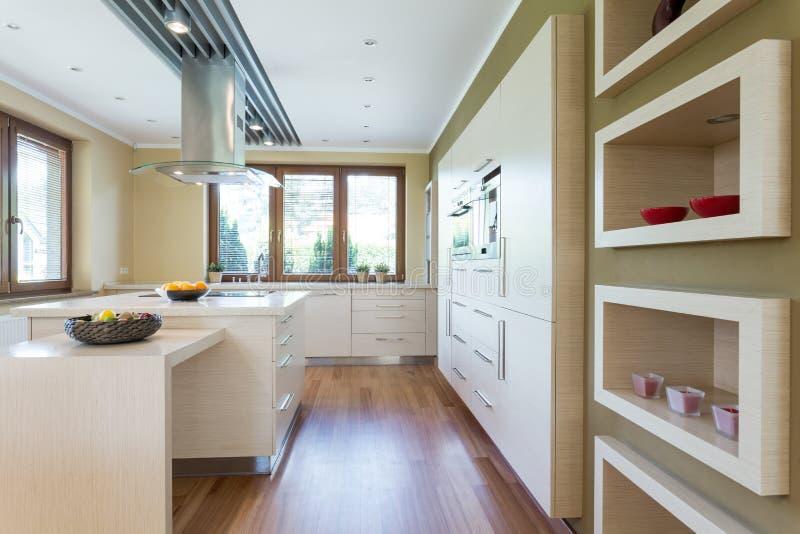 Modernt kök med vita inpassade kabinetter arkivbild