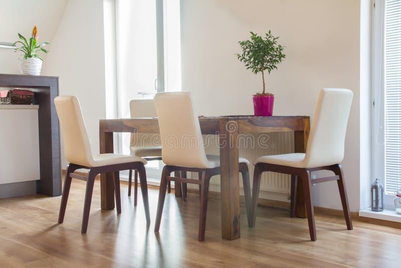 Modernt köksbord med stolar royaltyfri foto