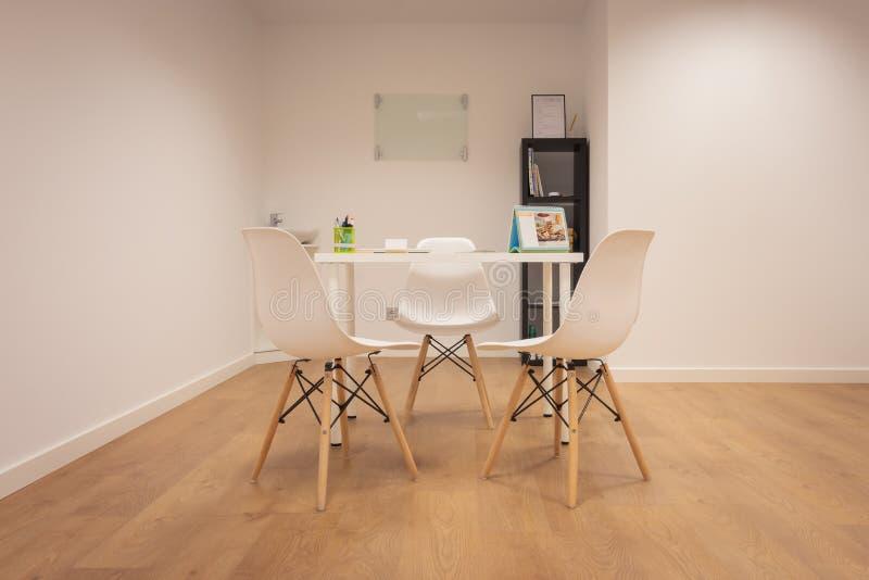 modernt kontor M?blemangupps?ttning med tabellen och stolar Inre av det minimalist kontoret med vita v?ggar, tr?golv, tr? och vit royaltyfri bild