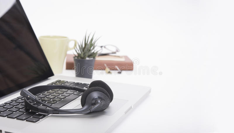 Modernt kontorsskrivbord med datoren, anteckningsbok, hörlurar med mikrofon, pappers- bok arkivfoton
