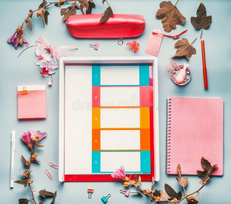 Modernt kvinnligt inrikesdepartementetskrivbord i rosa röd färg med blommor, tillbehör och stadsplanerareplånboken på blå bakgrun royaltyfri foto
