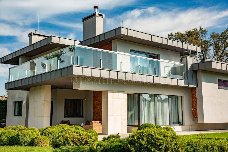 Modernt landshus med den stora gräsmattan och ett trästaket Framme av huset finns det en dold terrass med en vardagsrumzon royaltyfria foton