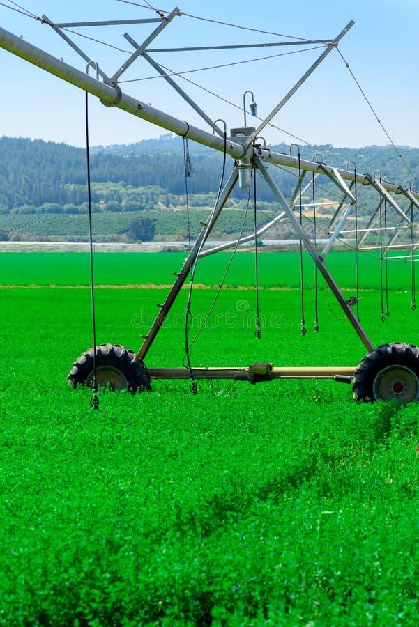 Modernt lantbruk Centralt sv?ngtappbevattningsystem i ett gr?nt f?lt royaltyfria foton