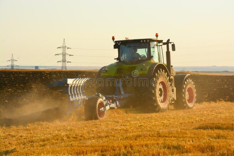 Modernt lantbruk med traktoren i plogat fält arkivfoton