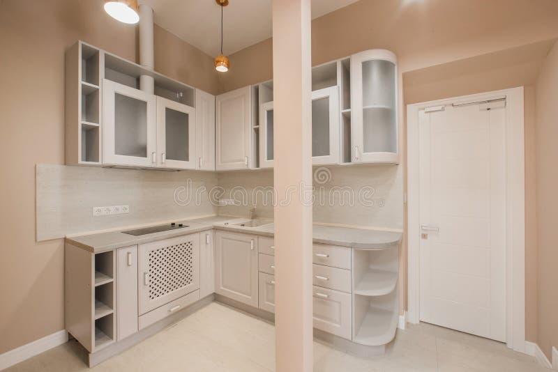 Modernt litet kontorskök med trämöblemang, inbyggd elektrisk utrustning och en vask för tvättande disk fotografering för bildbyråer
