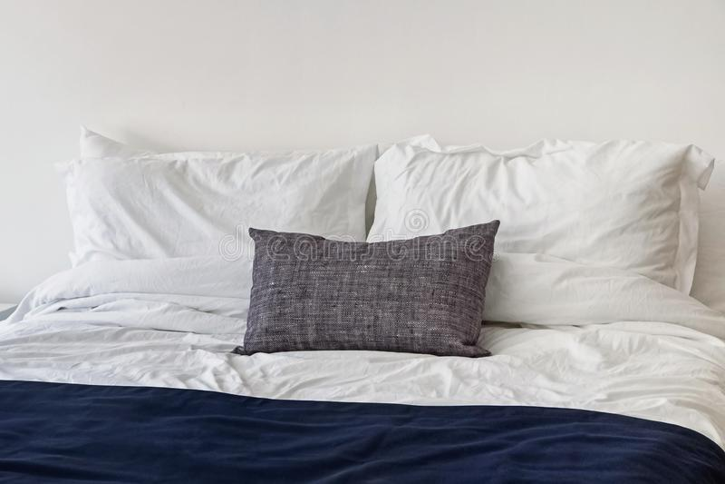 Modernt ljust minimalist sovrum med vita bedsheets arkivbild
