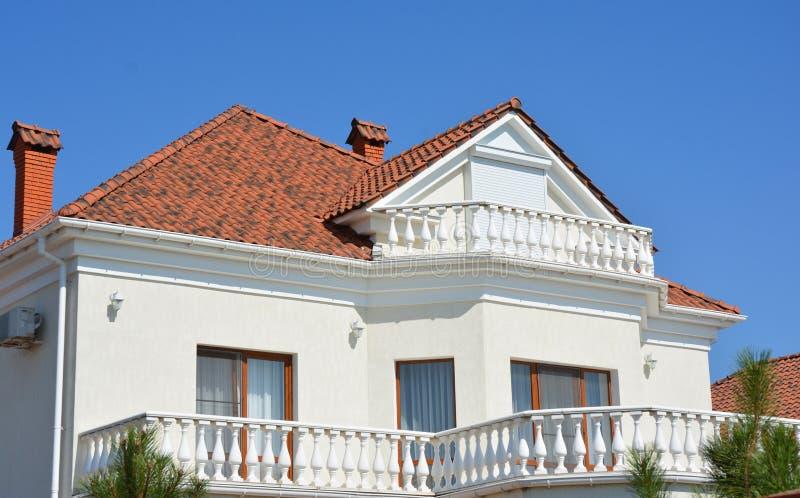Modernt lyxigt hus med lerataktegelplattor, stupränna, utomhus- belysning, loftfönster, balkong royaltyfri bild