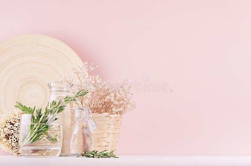 Modernt mjukt ljus - rosa pastellfärgad hemmiljö med den gröna växten, torkade vita blommor, beige bambuplatta på vit wood bakgru royaltyfria foton