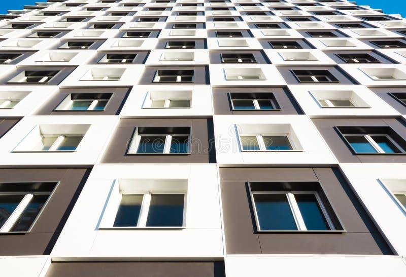 modernt nytt för hyreshus Foto av ett högväxt flerbostadshus med balkonger mot en blå himmel royaltyfri bild