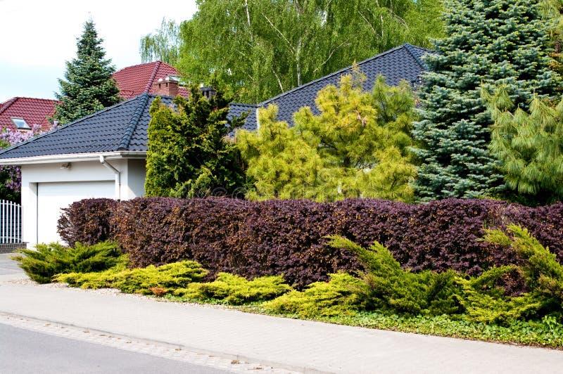 Modernt privat hus med den frodiga trädgården arkivbild