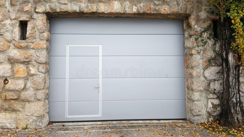 Modernt rulla upp garagedörrar inom traditionell ram för stenvägg royaltyfria bilder