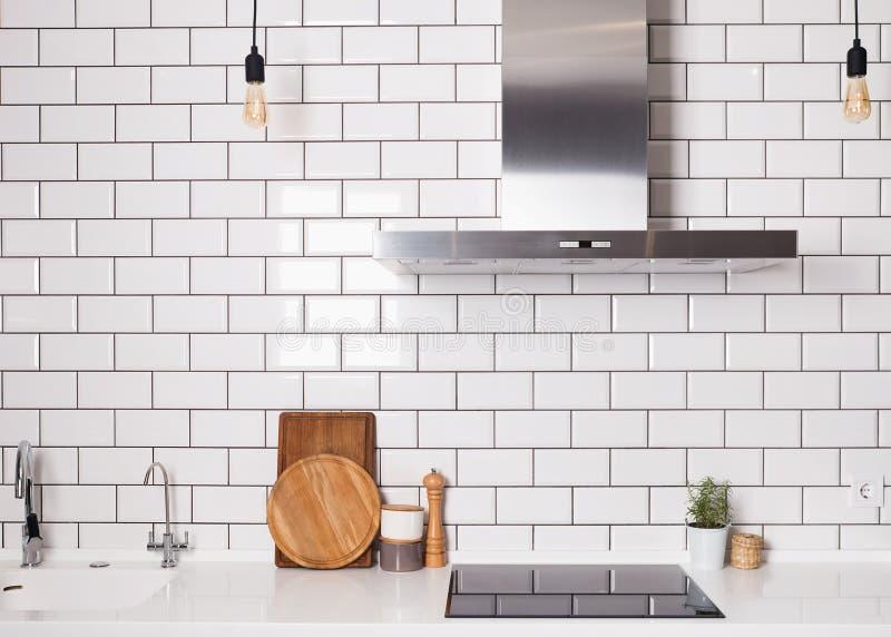 Modernt rymligt kök med den vita tegelstentegelplattaväggen fotografering för bildbyråer