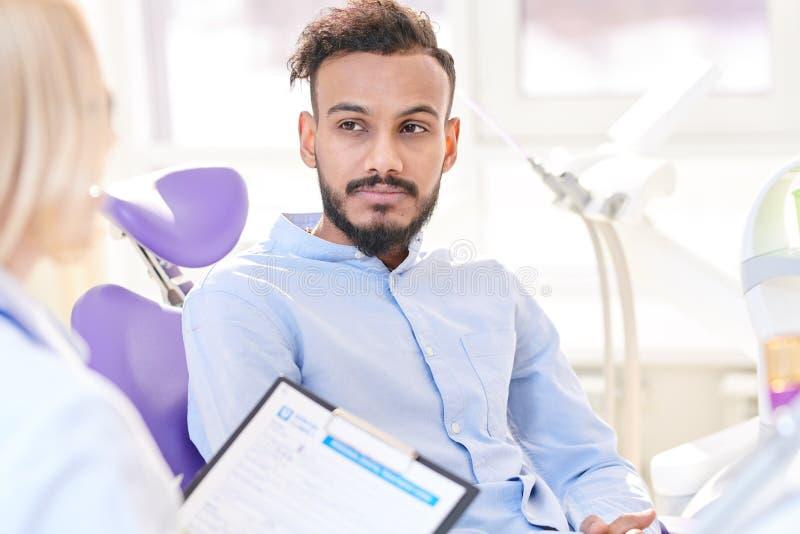 Modernt sammanträde för ung man i tand- stol royaltyfri foto